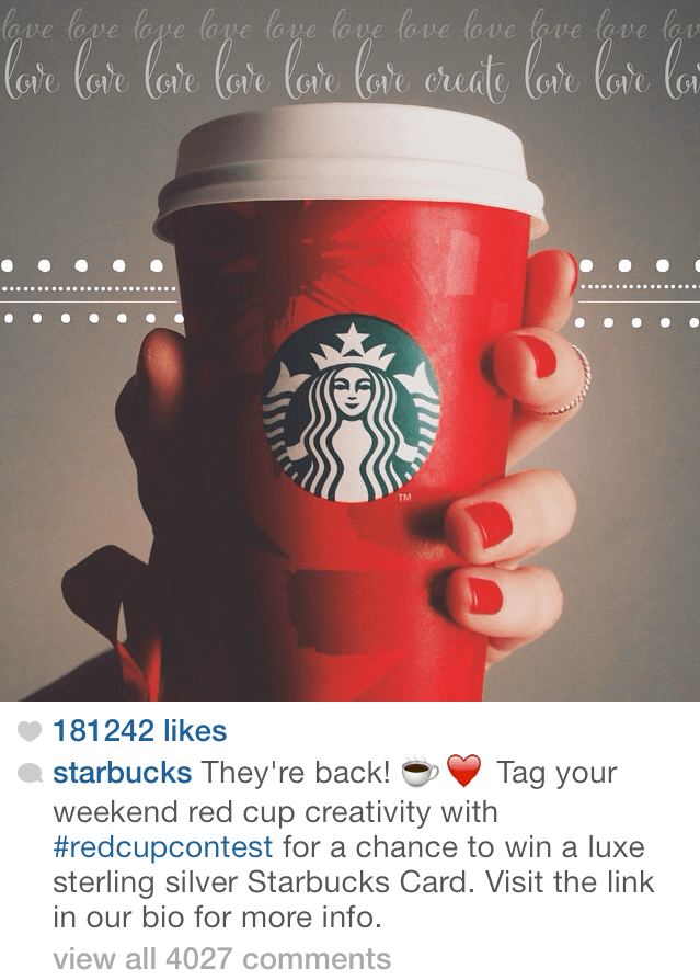 Hand holding a red holiday-themed Starbucks cup.