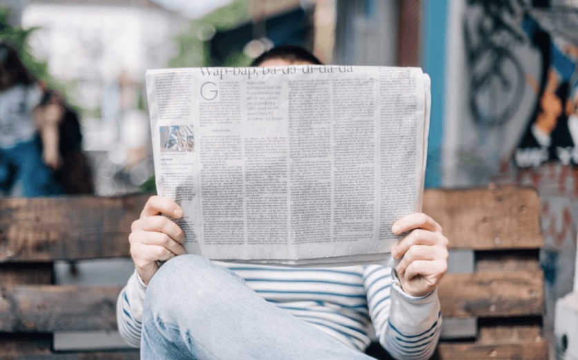 man sitting on bench reading a newspaper with an attention-grabbing headline