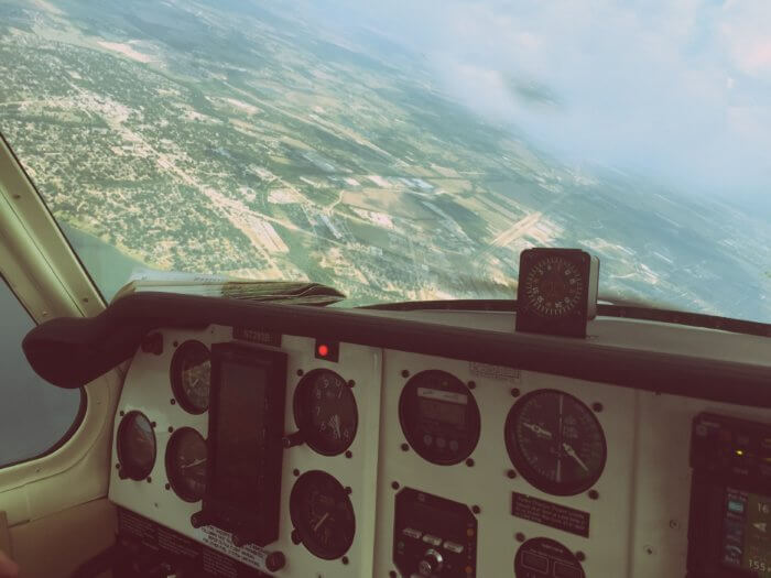 Data mistakes can be avoided with a strong dashboard, like this plane's dashboard and controls with a verdant landscape